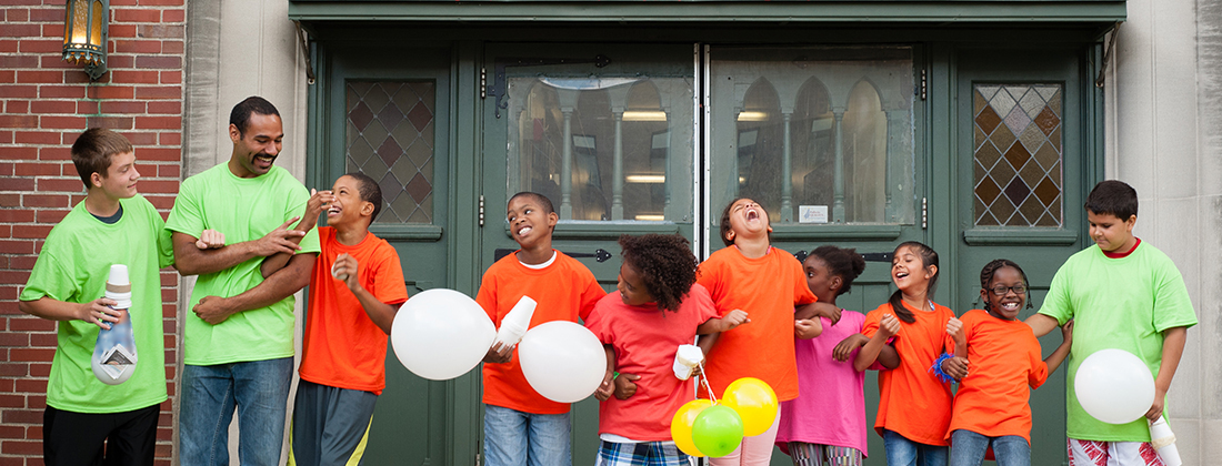Group of kids with balloons laughing with their afterschool teacher